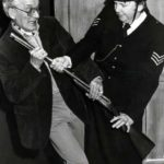 Col. Wagstaffe (Ted Younghusband) Struggles With Sergeant Fire (Margaret Yearsley) For The Shotgun!