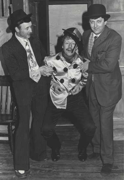 Flash Harry (Derek Dearne) and Alf Tubbe (Keith Beattie) carry jockey Fred Fipps (Bob Johnson) back into the room.