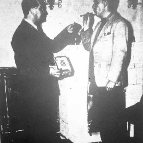 The General (M.Hicks) As Host Lights A Cigar For American Guest Sam Goulansky (Ted Younghusband)
