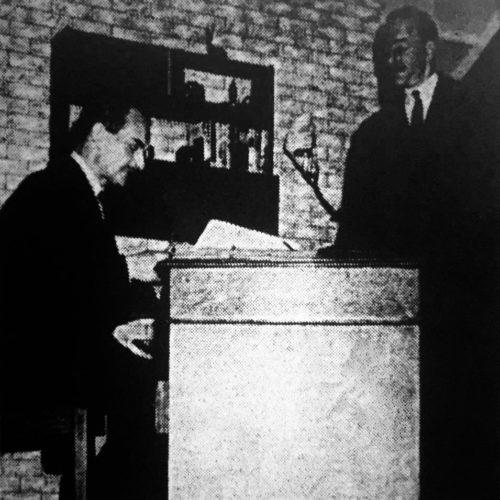 The Inspector (John Gale) Checks Charles Norbury's (D.H. Evans) Gun Licence